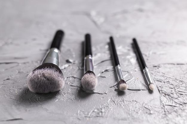 Blick von oben auf die make-up-pinsel auf grauem hintergrund.