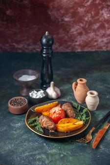 Blick von oben auf die mit kartoffeln und tomaten gebackenen fleischkoteletts, die mit grünem besteck serviert werden, gewürzt holzhammerknoblauch auf mischfarbenhintergrund