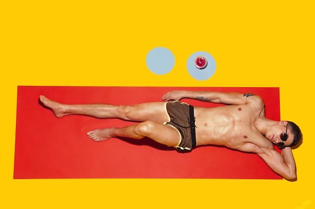 Blick von oben auf die ruhe des jungen kaukasischen männlichen models auf dem strandresort?