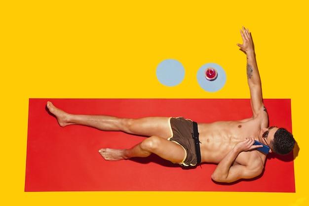 Blick von oben auf die ruhe des jungen kaukasischen männlichen models im strandresort?