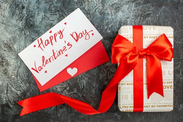 Blick von oben auf die schöne geschenkbox, die mit rotem band zum valentinstag auf eisigem dunklem hintergrund gebunden ist