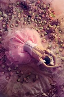 Blick von oben auf die schöne junge frau im rosa ballett-tutu, umgeben von blumen