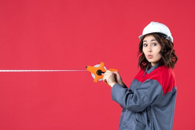 Blick von oben auf die sich wundernde architektin in uniform mit schutzhelmöffnungsmaßband auf isoliertem rotem hintergrund