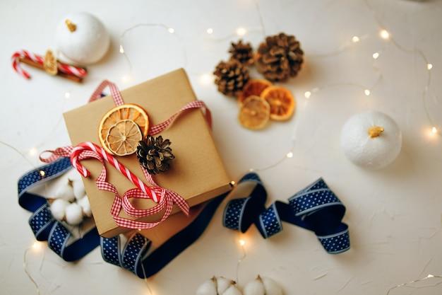 Blick von oben auf die weihnachtsgeschenkbox und dekorationen auf weißem strukturiertem tisch zuckerstange bunte bänder g...
