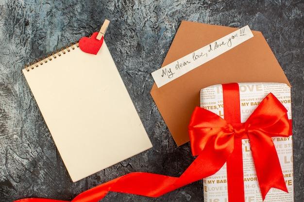 Blick von oben auf die wunderschön verpackte geschenkbox, die mit rotem band auf umschlag mit liebesbrief-spiralnotizbuch auf eisigem dunklem hintergrund gebunden ist