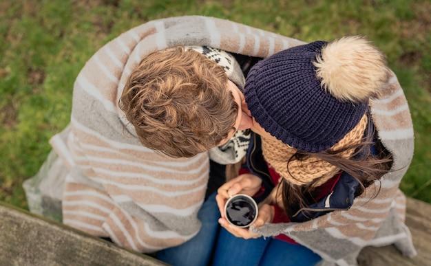 Blick von oben auf ein junges paar unter gestreifter decke und mit heißem getränk, das sich an einem kalten tag im freien küsst