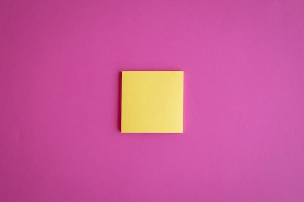 Blick von oben auf eine gelbe leere papier-post-it-notiz auf rosafarbenem hintergrund mit kopienraum