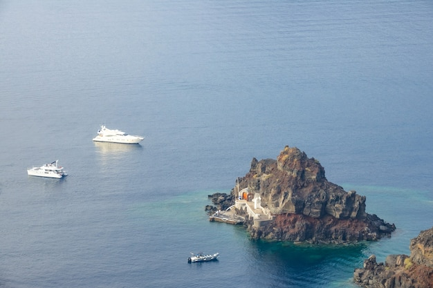 Blick von oben auf eine kleine felseninsel mit pier. zwei yachten und ein vergnügungsmotorboot vor anker in der nähe
