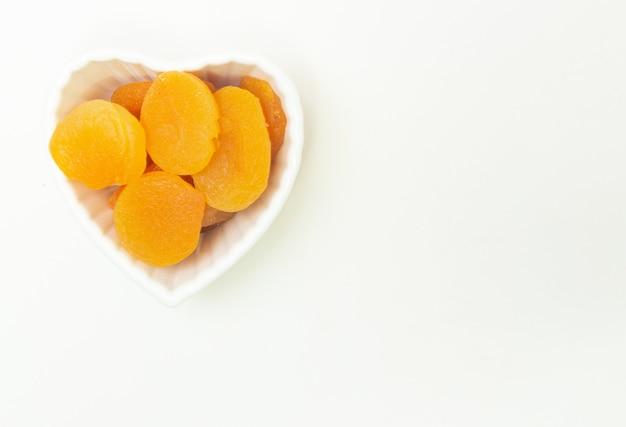 Blick von oben auf eine kleine weiße schüssel voller aprikosen