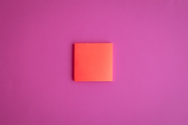 Blick von oben auf eine orangefarbene leere papier-post-it-notiz auf rosafarbenem hintergrund mit einem kopienraum