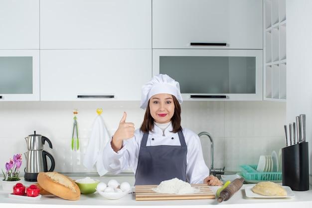 Blick von oben auf eine selbstbewusste köchin in uniform, die hinter dem tisch mit schneidebrett-brotgemüse steht und in der weißen küche eine gute geste macht