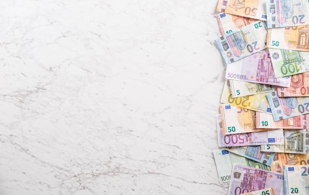 Blick von oben auf einen haufen euro-banknoten auf marmortisch.