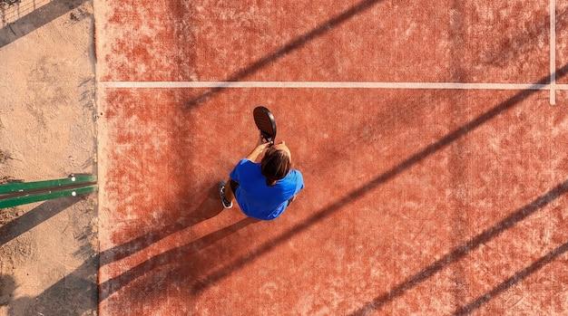 Blick von oben auf einen padelspieler, der in seiner position darauf wartet, den ball zu schlagen. außenplatz.