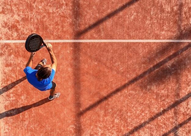 Blick von oben auf einen professionellen paddle-tennisspieler, der gerade den ball mit dem schläger geschlagen hat. padel-match auf einem außenplatz.