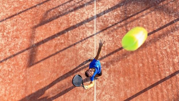 Blick von oben auf einen professionellen padel-spieler, der den ball während eines padel-matches schlagen wird. der ball ist sehr nah an der kamera.