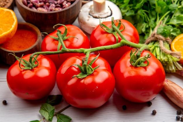 Blick von oben auf frische tomaten mit stiel braune bohnenbündel aus grünen pilzen auf weißem hintergrund
