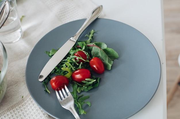 Blick von oben auf gesunde tomaten und grüns, die auf grauem teller in der küche liegen. leckeres frisches gemüse, messer und gabel liegen auf dem tisch im café. konzept der küche, ernährung und ernährung.
