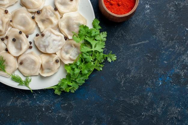 Blick von oben auf köstliche gebackene knödel in der platte zusammen mit pfeffer und gemüse auf einem dunkelgrauen schreibtisch