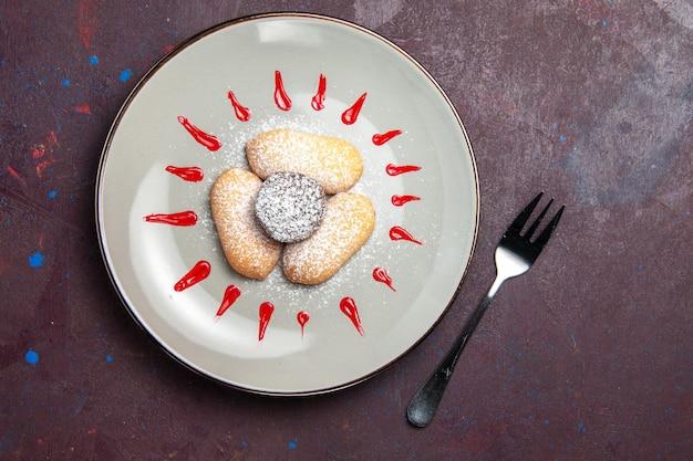 Blick von oben auf leckere kekse mit zuckerpulver und rotem zuckerguss im teller auf schwarz