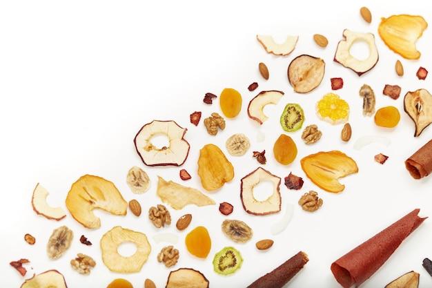 Blick von oben auf ordentlich gestapelte fruchtpastille in verschiedenen farben und mandeln, orange, getrocknete aprikose, rosinen, walnüsse, getrocknete äpfel und kiwi auf weiß