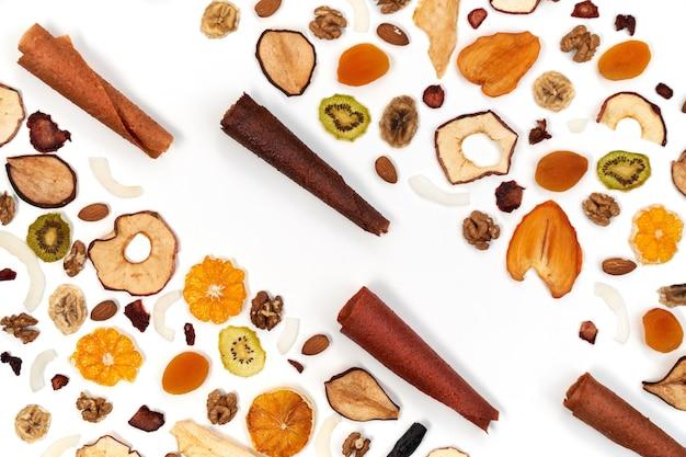 Blick von oben auf ordentlich gestapelte fruchtpastillen in verschiedenen farben und mandeln, orange, getrocknete aprikose, rosinen, walnüsse, getrocknete äpfel und kiwi auf weißem hintergrund. konzept der gesunden snacks.