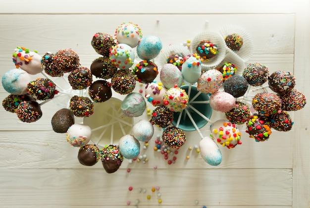 Blick von oben auf schöne bunte cake pops auf holztisch