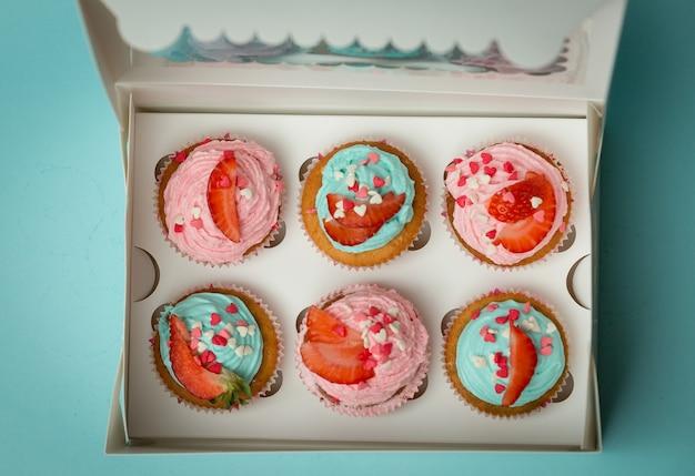 Blick von oben auf schöne bunte cupcakes mit streuseln und erdbeeren im karton