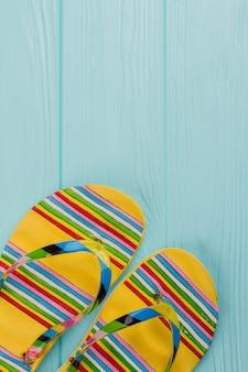 Blick von oben helles paar flip-flops auf blauem holztisch. kopieren sie platz im oberen teil.