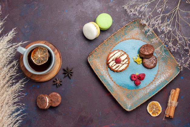 Blick von oben kleiner cremiger kuchen mit schokoladenkeksen und tasse tee auf dem dunklen oberflächenkeks süßer kuchen-zucker-keks-kuchen