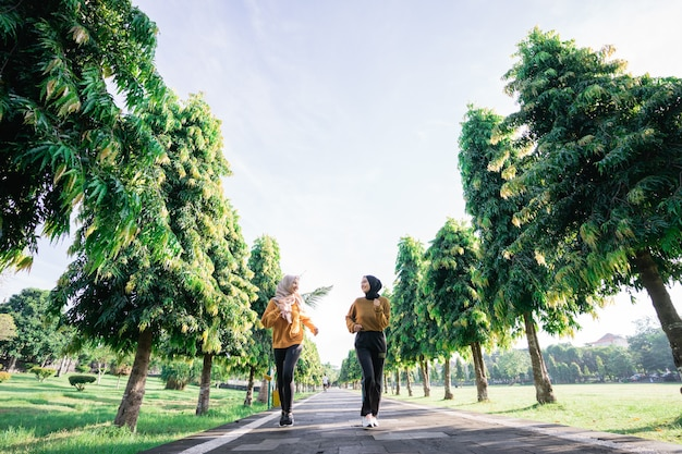 Blick von unten auf zwei mädchen im schleier, die im freien sport treiben, während sie zusammen im garten mit copyspace joggen