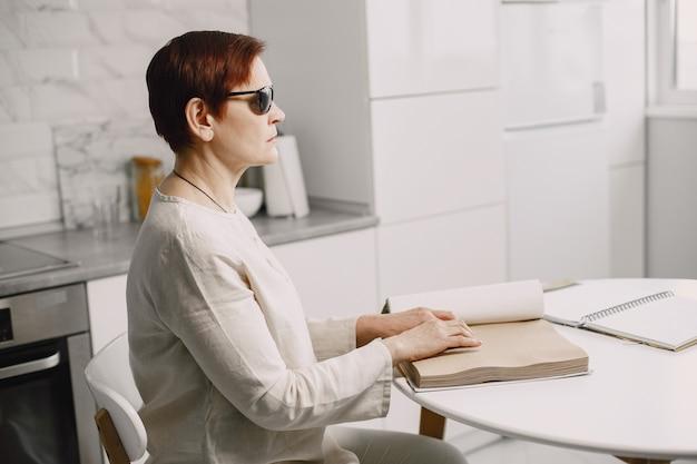 Blinde reife frau, die braillebuch zu hause liest