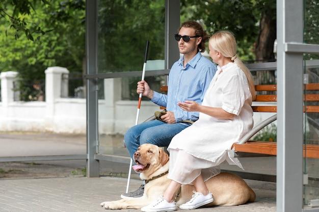 Blinder junger mann mit blindenhund und mutter, die auf bus draußen warten