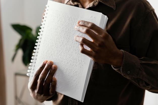 Blinder mann, der braille mit händen liest