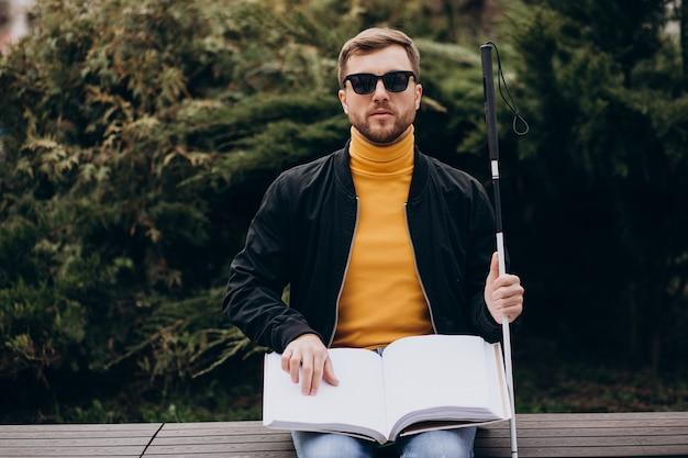 Blinder mann, der durch berühren des braillebuchs liest