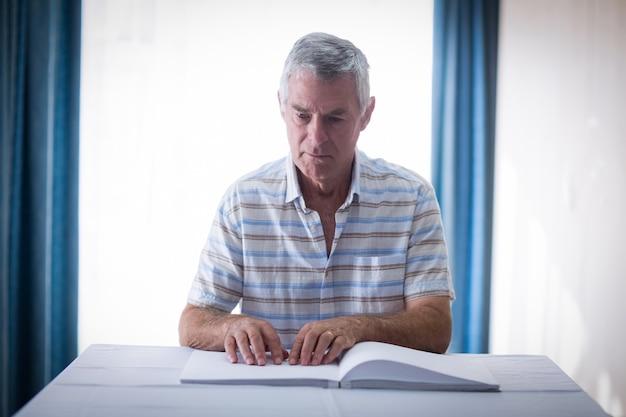 Blinder mann, der ein blindenschrift-buch liest