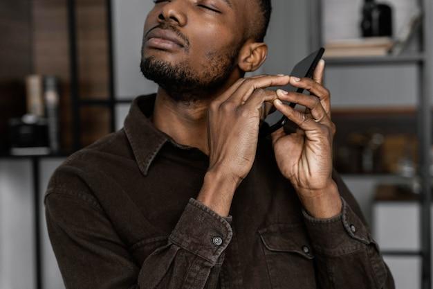Blinder mann, der smartphone nah oben hält