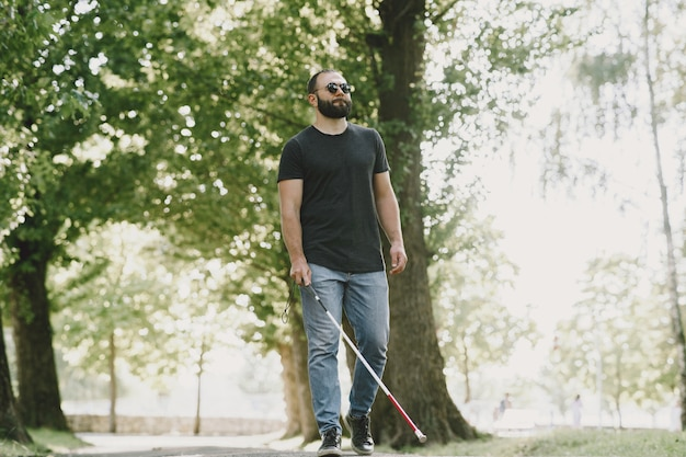 Blinder mann. menschen mit behinderung, behinderte und alltag. sehbehinderter mann mit spazierstock, absteigende stufen im stadtpark.