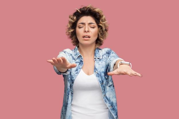 Blindheit. porträt von sorgen oder aufmerksamen jungen frauen mit lockiger frisur in lässigem blauem hemd, die mit geschlossenen augen stehen und versuchen, etwas zu berühren. indoor-studioaufnahme, isoliert auf rosa hintergrund.