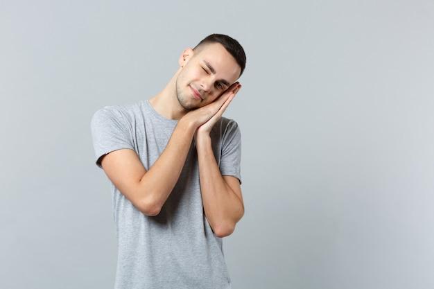 Blinzelnder junger mann in freizeitkleidung, der sich ausruht, mit den händen in der nähe des gesichts schläft und die augen geschlossen hält