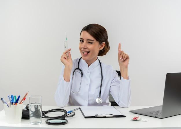 Blinzelte junge ärztin, die medizinische robe mit stethoskop trägt, das am schreibtisch sitzt, arbeitet am computer mit medizinischen werkzeugen, die spritzenpunkte oben halten und zunge auf weißer wand mit kopienraum zeigen