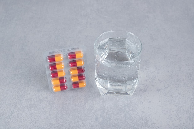 Blister mit medizinpillen mit einem glas reinem wasser