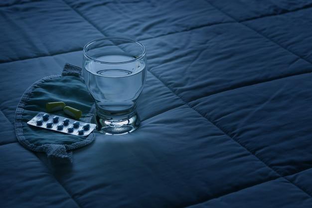 Blisterpackung mit schlaftabletten, augenbinde und glas wasser