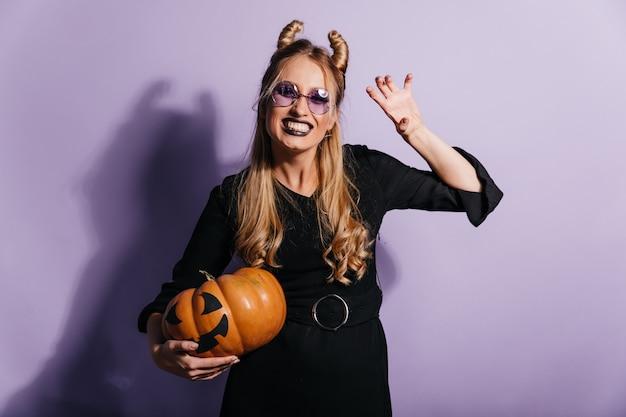 Blithesome blondes mädchen im hexenkostüm, das karneval genießt. innenaufnahme der lächelnden sorglosen dame mit halloween-kürbis, der auf lila wand steht.