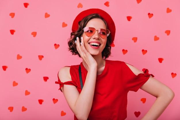 Blithesome emotionale frau, die unter rotem konfetti aufwirft. glückliches französisches mädchen, das spaß hat