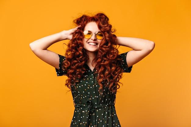 Blithesome europäisches mädchen, das ingwerhaar berührt und lacht. studioaufnahme der fröhlichen jungen frau in der sonnenbrille, die auf gelbem hintergrund aufwirft.