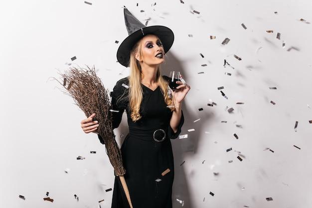 Blithesome junge hexe, die wein trinkt. sorglose frau in halloween-kleidung, die auf partei aufwirft.