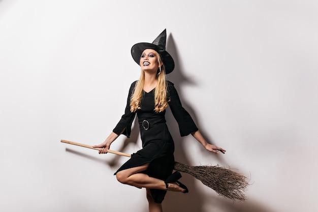 Blithesome langhaarige frau, die spaß in halloween hat. nettes blondes mädchen im hexenhut, der an karnevalsparty lächelt.