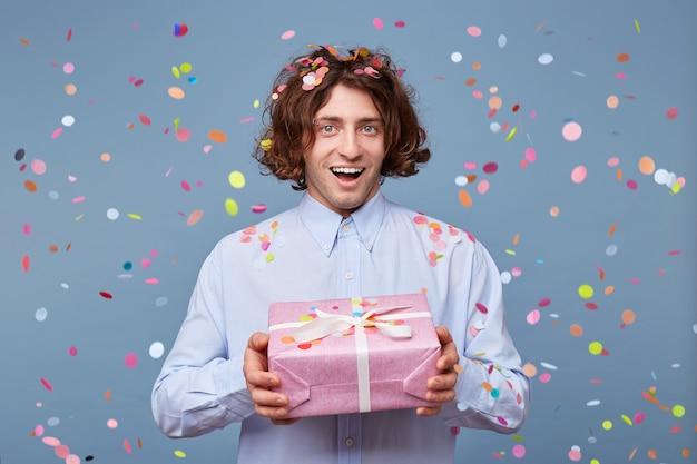 Blithesome langhaariger kerl, der geburtstag mit geschenken genießt