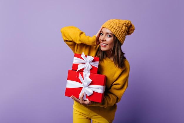 Blithesome mädchen im gelben hut, der sich auf weihnachten vorbereitet. innenporträt der fröhlichen kaukasischen dame, die auf purpur mit neujahrsgeschenken aufwirft.