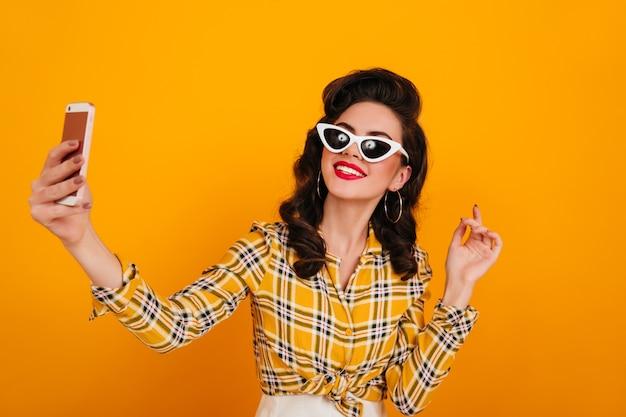 Blithesome pinup girl in sonnenbrille nimmt selfie. frau im karierten hemd, das auf gelbem hintergrund mit smartphone aufwirft.